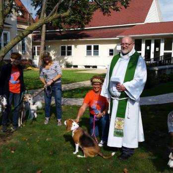 Fr. Tom posing with more dogs and people in the church courtyard.