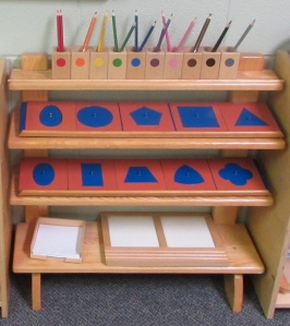 Metal insets on shelves with colored pencils and tracing trays.