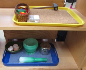 A yellow tray with a cork board, shapes, tacks, and hammer; a blue tray with eggshells and a mortar and pestle.