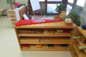 A shelf of Montessori sensorial materials including red rods, brown stair, and cylinders.