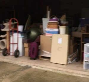 Boxes and other items piled in the old garage ready to load for moving.
