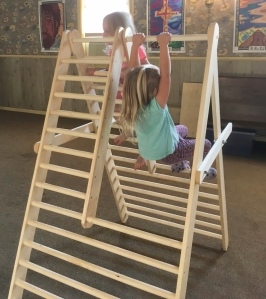 Children climbing and swinging on an a-frame