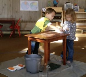 One child scrubs a table while another observes.