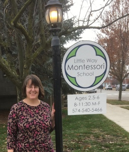 Marcy standing next to the school sign.