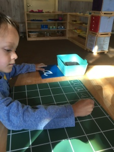 "Child practices forming the letter ""a"" on a gridded chalkboard."