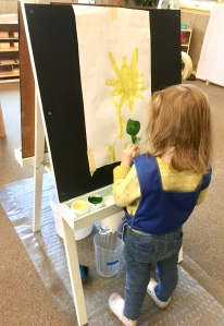 Girl painting at easel.
