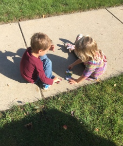 Two children playing with cars.